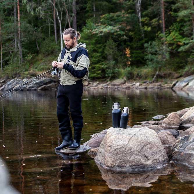 Fisker som har to termoser stående på en stein