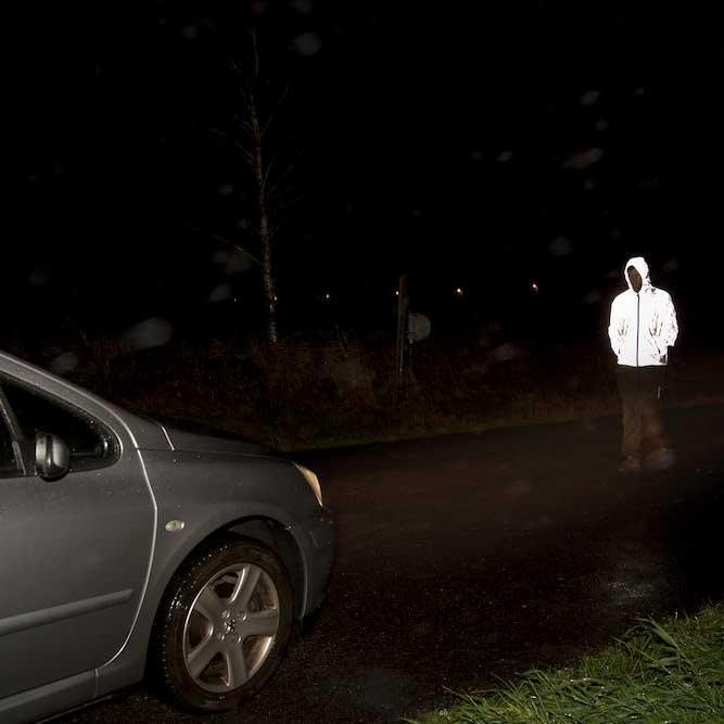 Hardy refleksjakke på modell forran frontlys på bil
